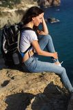 Pretty girl traveler is sitting on rock edge with backpack Stock Image