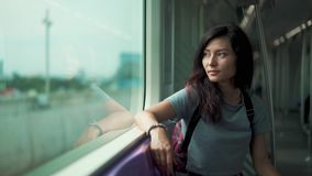 Pretty girl travelling in a train of underground. Beautiful young woman travelling in a train of underground and looking through the window stock footage