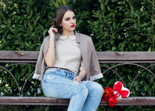 Pretty girl with tulips sitting on the bench Royalty Free Stock Images