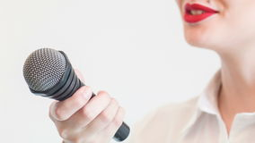 Pretty girl tv journalist is interviewing someone. Close up portrait of  beautiful woman tv reporter with red lips, who is smiling while holding the microphone stock footage