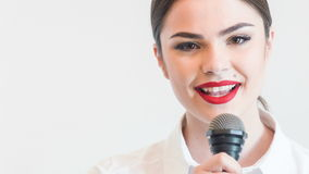 Pretty girl tv journalist is singing emotionally. Waist up portrait of beautiful woman tv reporter with pretty smile and red lips, who is singing very stock footage