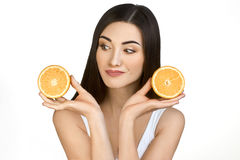 Pretty Girl with Two Halves of Orange in Hands on White Background. Young Woman with Dark Long Hair Holding Fruit Near Her Face. Isolated. Healthy Food Concept royalty free stock image