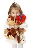 Pretty girl with two toy monkeys in hands Stock Image