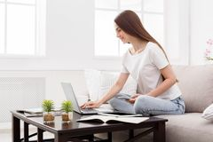 Pretty girl typing on laptop at home on the couch. Dark-haired girl in casual. Dark-haired girl texting on mobile and typing on laptop at home on the couch. Copy Royalty Free Stock Image