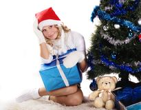 Pretty girl under christmas tree. Pretty girl wearing knitted mittens and santa hat sitting under christmas tree with gifts Stock Photography