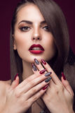 Pretty girl with unusual hairstyle, bright makeup, red lips and manicure design. Beauty face. Art nails Royalty Free Stock Images