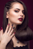 Pretty girl with unusual hairstyle, bright makeup, red lips and manicure design. Beauty face. Art nails. Stock Photography