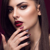 Pretty girl with unusual hairstyle, bright makeup, red lips and manicure design. Beauty face. Art nails. Royalty Free Stock Photography