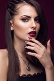 Pretty girl with unusual hairstyle, bright makeup, red lips and manicure design. Beauty face. Art nails. Stock Images