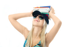 Pretty girl unwilling to study. Young blond woman with a lot of books on her head against white background Royalty Free Stock Photo