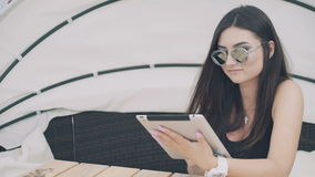 Pretty girl uses digital tablet resting on beach lounge in 4K.  stock footage