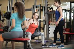 Pretty girl using barbell in gym. Trainer keep watch over her Royalty Free Stock Photos