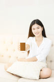 Pretty girl using her smartphone on couch Stock Image