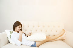 Pretty girl using her smartphone on couch Stock Photos