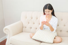 Pretty girl using her smartphone on couch at home in the living Stock Photo