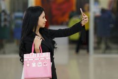 Pretty girl using her smartphone to take a selfie photo. Woman with shoppping bags in mall. Pretty girl using her smartphone to take a selfie photo. Woman with Royalty Free Stock Photos