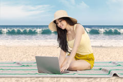 Pretty girl using laptop on the beach. Portrait of a beautiful girl sitting on the mat while wearing hat and using laptop at beach Royalty Free Stock Photo