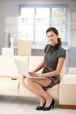 Pretty girl using laptop at home smiling. Pretty girl sitting on sofa at home, using laptop, smiling stock image