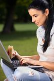 Pretty girl using laptop in park Royalty Free Stock Images