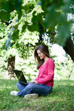 Pretty girl using laptop in park Stock Images