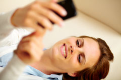 Pretty girl using a mobile phone at home Stock Image