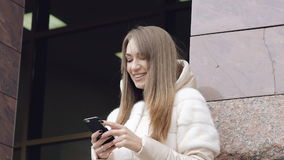 Pretty girl using phone near the office outdoor. In full HD stock video