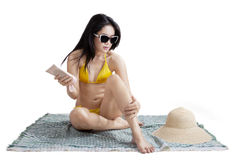 Pretty girl using suntan lotion Royalty Free Stock Photos