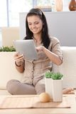 Pretty Girl Using Tablet At Home Smiling Royalty Free Stock Image
