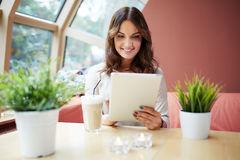 Pretty girl using tablet at cafe Royalty Free Stock Image