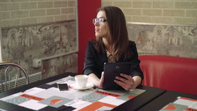 The pretty girl using a tablet in a modern comfortable cafe 4k.  stock footage