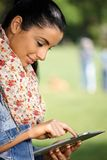 Pretty girl using tablet outdoors smiling Stock Photos