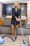 Pretty girl using vacuum cleaner at home Stock Photo