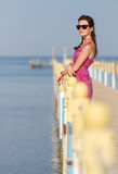 Pretty girl on vacation i standing at a pier enjoying sunshine. Stock Photos