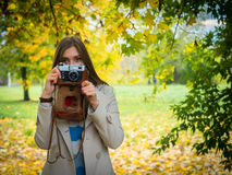 Pretty girl with vintage camera in park Stock Images