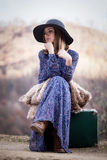Pretty girl with vintage case on a dirtroad Stock Image
