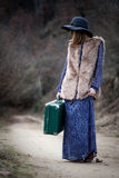 Pretty girl with vintage case on a dirtroad Stock Photo