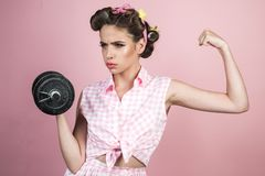 Pretty girl in vintage style. retro woman with dumbbell. Sport. pin up woman with trendy makeup. pinup girl with fashion. Hair. powerful housewife. Confident in royalty free stock image