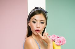 Pretty girl in vintage style. retro woman eating ice cream from flowers. pin up woman with trendy makeup. pinup girl royalty free stock photo