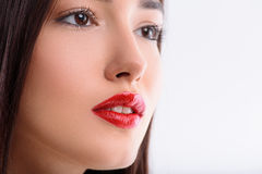 Pretty girl with voluptuous red lips. Close up of face of sensual young woman looking forward with desire. She has perfect make-up. Isolated and copy space in Stock Images