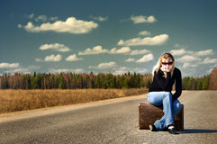 Pretty girl waiting. On the road with her baggage royalty free stock images