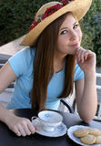 Pretty girl waiting fro tea to be served. Pretty girl wearing flowered straw hat and pale blue shirt looking coy as she waits for tea to be served at outdoor Royalty Free Stock Photo