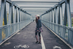 Pretty girl walking away on a bridge Stock Image