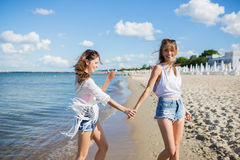 Pretty girl walking on beach holding hand with her friend stock photos