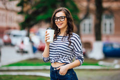 Pretty girl walking with a cup of coffee Stock Photos