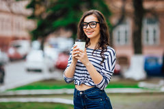 Pretty girl walking with a cup of coffee Stock Photography
