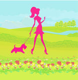 Pretty girl walking the dog Royalty Free Stock Images