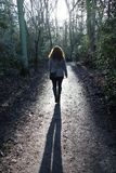 Pretty girl / woman walking in woods path road Royalty Free Stock Image
