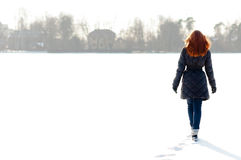 Pretty girl walking on frozen lake stock image