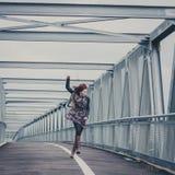 Pretty girl walking happy on a bridge Stock Image