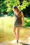 Pretty girl walking on river shore Royalty Free Stock Photography